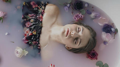 Attractive girl in bath with milk and fragrant buds of flowers. Spa treatments Live Action