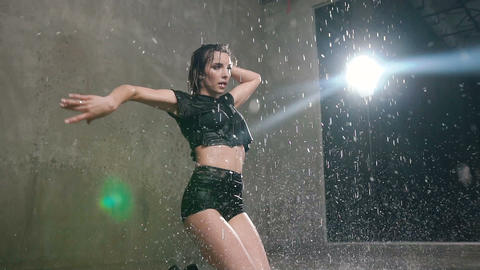Wet woman dancer in black body suit performs modern dance on the floor in the Live Action