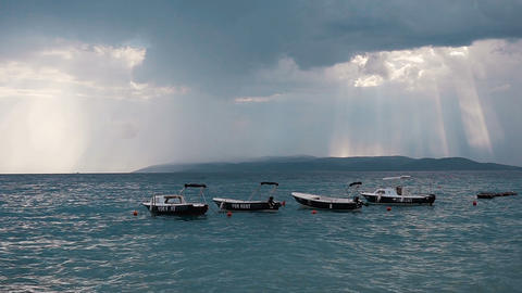 There are parked motor boats parked in the sea and rocking on waves. The rays of Footage
