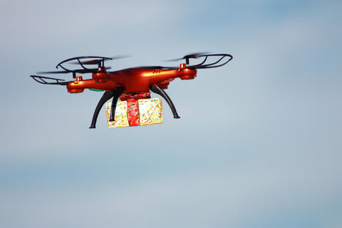 Orange drone with gift box on the cloudy sky background Photo