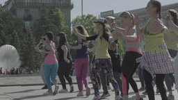 People are dancing (doing dance aerobics) day outdoors . Slow motion Footage