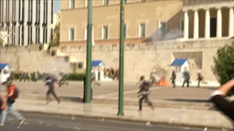 POLICE GIVE CHASE TO PROTESTERS THROWING PROJECTILES OUTSIDE GREEK PARLIAMENT stock footage
