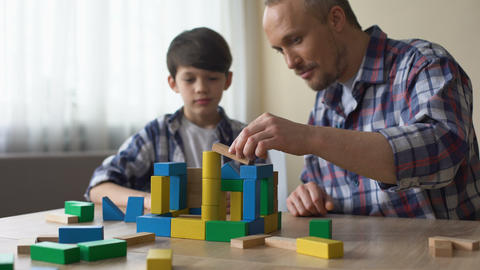 Caring daddy and his smiling son playing colored toy cubes at home, childhood Footage