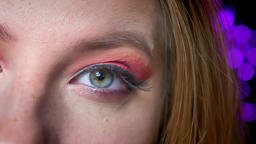 Closeup of stunning blue eyes makeup with pink shades and long eyelashes on the Footage
