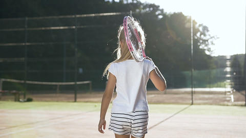 Little girl with tennis racket walking on the court 영상물