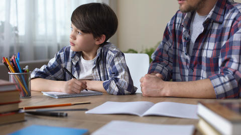 Bored little boy doing homework with strict father, sad child looking in window Live Action