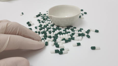 Manipulating white green capsules in the pharmacy laboratory Footage