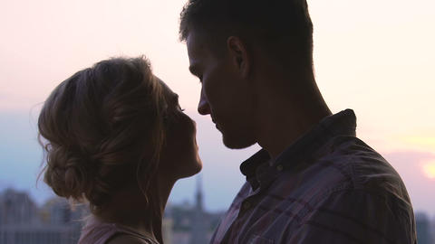 Young couple kissing on sky cityscape background, youth love, togetherness Live Action