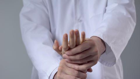 Traumatologist moving patient wrist, assessing severity of injury, closeup Footage