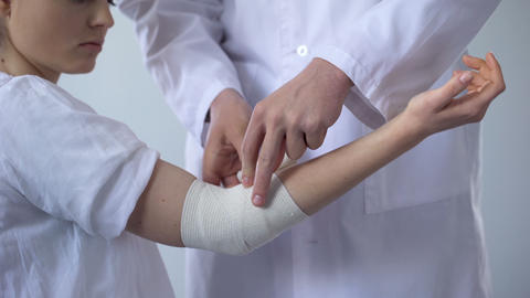 Doctor bandaging injured patient hand, first aid for sprain in trauma clinic Live Action