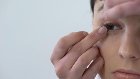 Young woman putting contact lens in her right eye, care and hygiene, closeup Footage