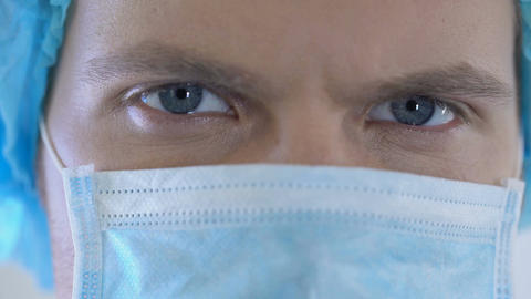 Competent handsome male physician with blue eyes looking at camera, closeup Live Action