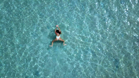 Aerial view. Beautiful young woman in white bikini floating on water surface in 영상물