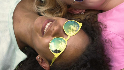 Two girls relaxing on grass, sky reflection in sunglasses, friendship and fun Footage