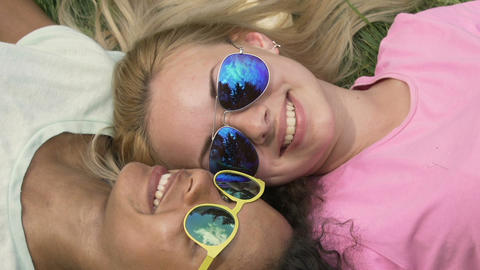 Beautiful smiling girls in sunglasses lying on grass, leisure time at campus Footage