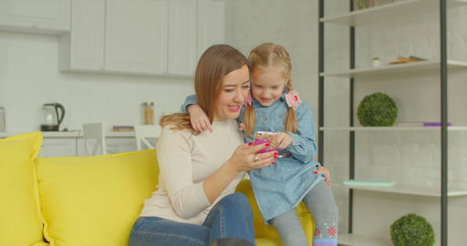 Mother and cute girl browsing online on cellphone Footage