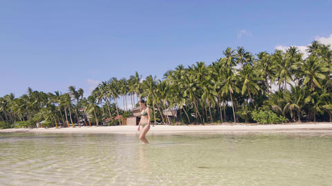 Happy woman in swimsuit running on sea at paradise beach on palm tree landscape Footage