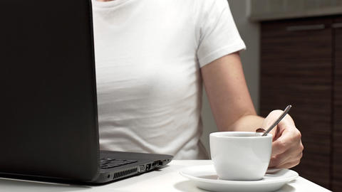 Woman works on her laptop at the workplace and drinks coffee, work at the office 영상물