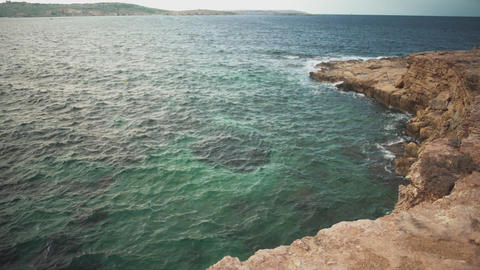 View of the sea and rocky cliff in sunny weather. Soft wave of blue sea Footage