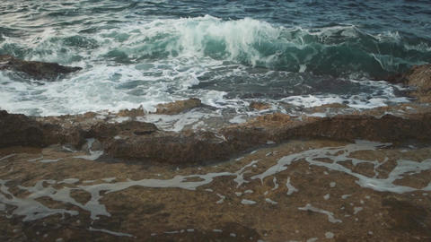 Foamy waves crashing on a rocky shore. Splashes of a sea wave scatter on the Footage