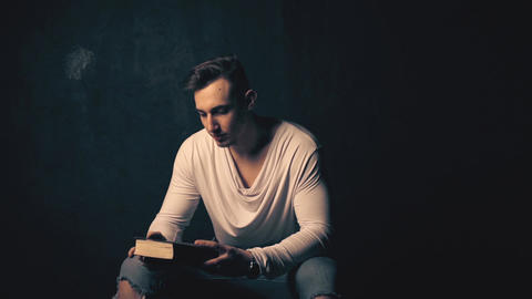 Young man reading an old book Live Action
