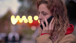 Side close-up portrait of young blonde caucasian girl talking on cellphone on Footage