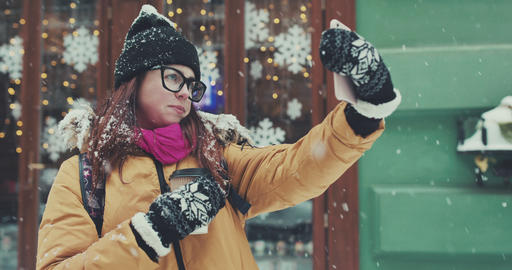 Beautiful girl makes a selfie at day lights background at winter Footage