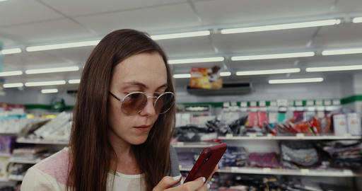 Woman Using the Phone in the Store Footage