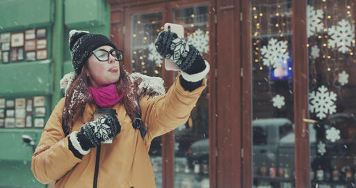 Happy girl makes a selfie in winter city. Girl makes selfie against the Footage