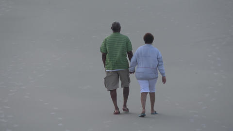 Old couple walking at the beach - DAYTONA BEACH, FLORIDA APRIL 14, 2016 Live Action