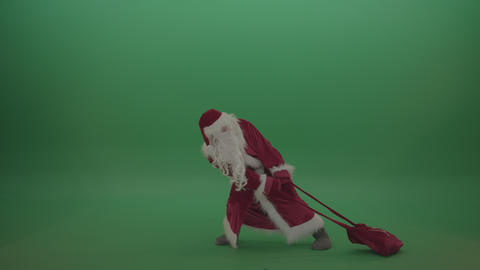 Santa drags the heavy gift bag over chromakey background Footage