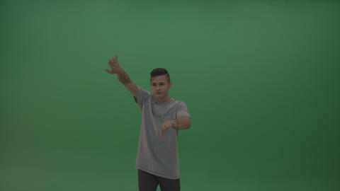 Boy in grey wear operates invisible screen over chromakey background Live Action
