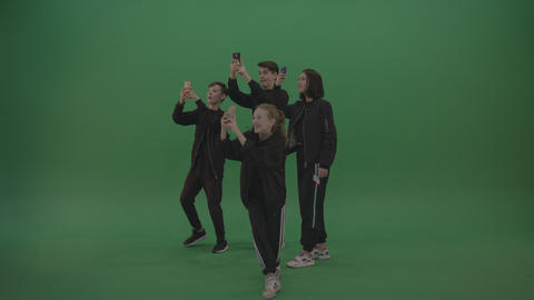 Four kids in black wears take pictures over chromakey background Footage