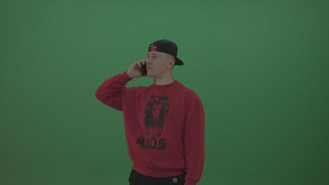 Man in red sweater speaks on the phone over chromakey background Footage