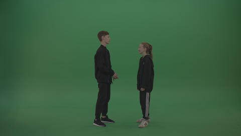 Two kids in black wear stare at each other over chromakey background Footage