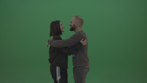 Two people in black and grey wear hug each other over chromakey background Footage