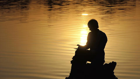 Dreamlike man reads a book on a lake bank at a sunset ビデオ