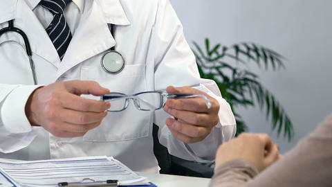 Close up of male ophthalmologist choosing eyeglasses for patient, checkup Live Action