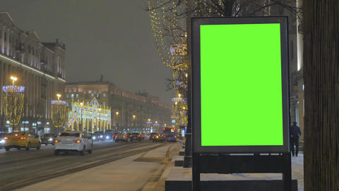 A big billboard with a green screen on the street decorated for the holiday Live Action