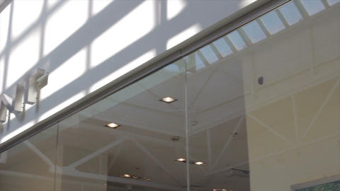 camera moves past shop window to shopping mall ceiling Footage