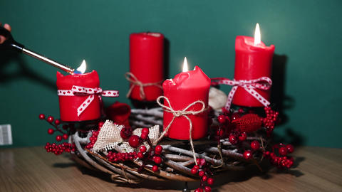 Modern Christmas wreath with four red candles on wooden surface with green Footage