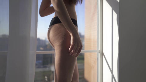Naked beautiful brunette with long hair stand near window inside house. Sensual Footage