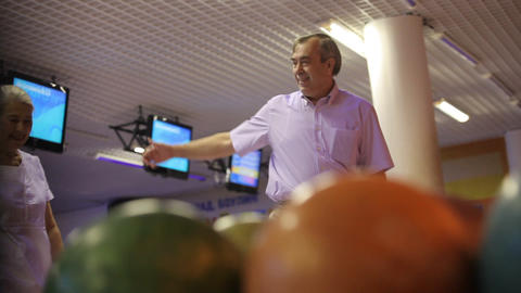 Man supports wife in bowling Live Action