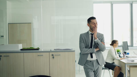 Stressed young man in suit is standing in office waiting for job interview while Footage
