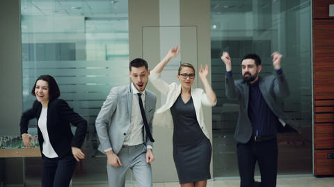 Joyful youth colleagues are dancing in office hall having fun together and Live Action