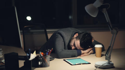 Tired guy in suit in sleeping on work desk in office late at night after busy Live Action
