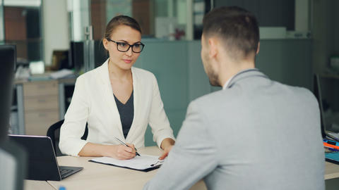 Pretty woman recruiter is talking to male candidate during job interviewer in Footage