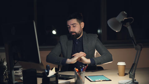 Tired young man in suit and tie is working on computer in office at night Live Action