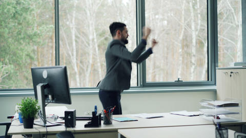 Handsome young man office worker is dancing in office and taking off jacket Footage