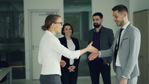 Happy guy in suit is getting job in company after successful interview, shaking Footage